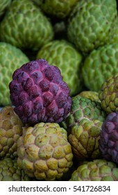 Red custard apple fruit with green custard apple background in fresh market .