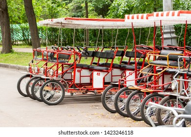 Red cyclo velomobiles with a canopy for the whole family. Parked rental tourist trike vehicles. Ecological transport for walking and sports. Bicycles for rent