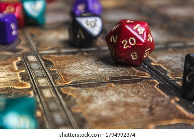 Red d20 die showhing a 20. Set of role playing dice on a gaming mat.