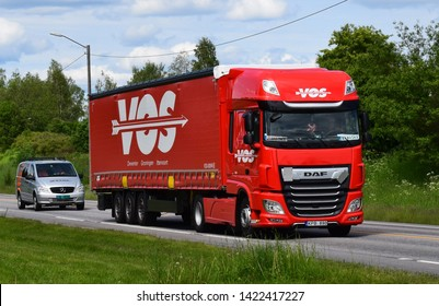 Red DAF truck vehicle with VOS sign on the road transporting goods for delivery - sunny and summer season - Kongsvinger, Norway (11th june 2019)