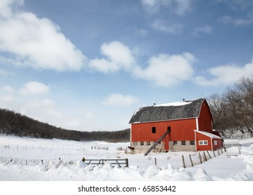 A red dairy barn in a very rural county scene in the middle of a snowy field.
