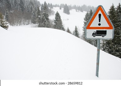 Red danger sign on road covered with snow