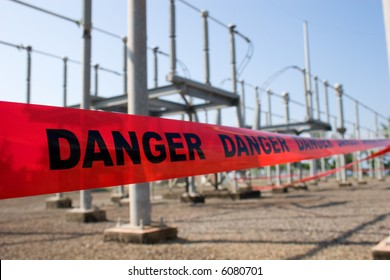 Red danger tape barricade for high voltage safety with switch yard at the background