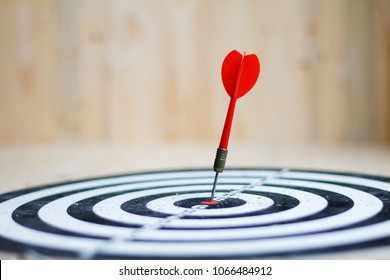 Red dart arrow hit the center target of dartboard metaphor marketing competition concept, on wood background