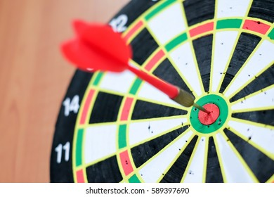 Red dart arrow hit in the target center of dartboard