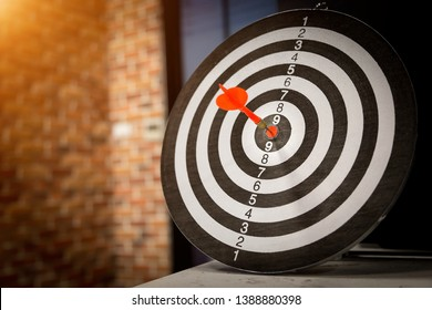 Red dart arrow hitting in the target center of dartboard on bullseye with sun light vintage style, Target marketing and business success concept - Image.