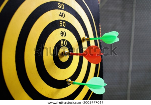 Red dart arrow hitting in the target center of dartboard with nice back ground. Business success concept shown with Dart and Dartboard. Marketing Aim concept. Symbolic representation of achieving goal
