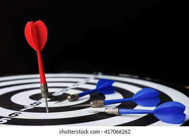 Red dart arrow on the target with dartboard, leadership concept, high contrast and dark lighting tone