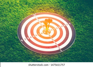 Red dart arrows hit on bulleyes of dartboard on nature background to represent that the business reached the target of company. Target and goal as concept.