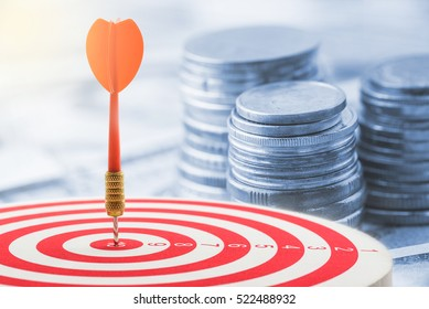 Red dart hit in the center of a target with stack of coins behind. A idea about money / currency investment that must decide or think carefully / thoroughly before putting money in these risky assets.