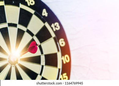 Red dart on board right direction hit target goal. Competition game to win focus on achievement with smart thinking planning accurate strategy. Outstanding perfect performance with concentrate concept