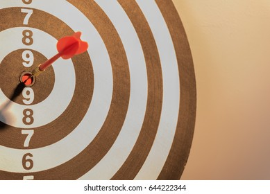 Red dart target arrow hitting on bullseye with sun light vintage style,metaphor to target marketing and business success concept