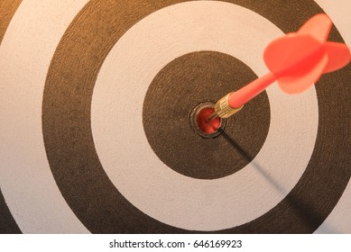 Red dart target arrow hitting on bullseye with sun light vintage style, Target marketing and business success concept