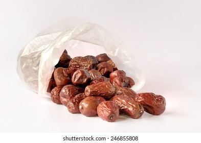 Red dates from transparent plastic bag on white background.