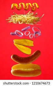 Red deconstructed hot dog sandwich. Hot dog with sausage, cucumber, onion, cheese, mustard on red background.