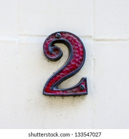 red decorated house number two on a white wall