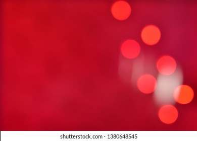 Red delicate circles bokeh from elegant holiday decorations on a homogeneous red background