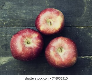 Red delicious apple on a wooden surface - vintage look