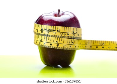 Red delicious apple with a tape measure around it showing a 'weight loss' or 'diet' or 'eat healthy' theme