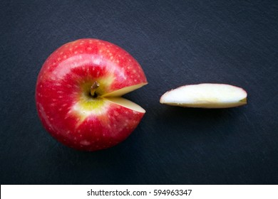 Red Delicious and Pink Lady Apples with slice cut out Apple Pac-Man on natural slate background