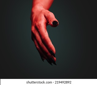 Red demon hand with handshake gesture on dark background. Deal with the Devil. Halloween or horror theme