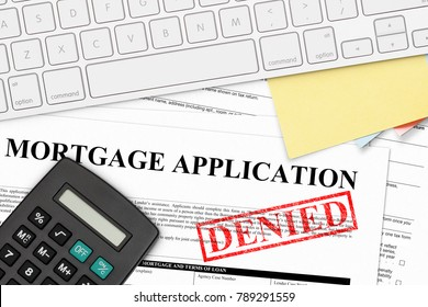 RED DENIED RUBBER STAMP ON MORTGAGE APPLICATION WITH CALCULATOR, COMPUTER KEYBOARD, AND PAPER NOTES
