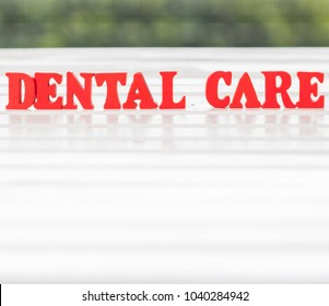 Red 'Dental Care' words with bokeh background on white wooden table