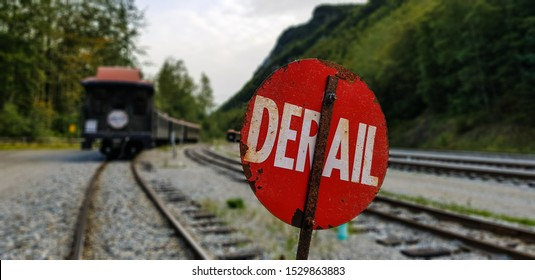Red derail sign on railroad tracks and blurred train as background