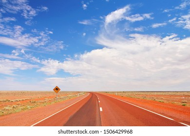 Red desert of Australia and yellow road sign
