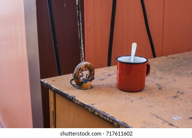 Red desolate cup of tea on an orange background. Tin coated enamel mug. Outdoor.
