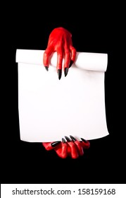 Red devil hands holding paper scroll for deal with devil concept, isolated on black background