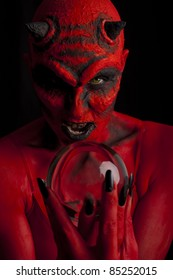 Red devil woman with her crystal ball, black background.