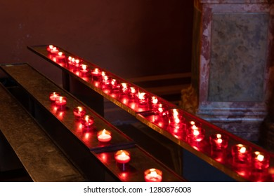 Red devotional candles in a church