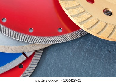 Red diamond wheels for granite and stone, blue for concrete, reinforced concrete, yellow for grinding concrete and stone, silver for cutting ceramic tiles on a slab of gray sandstone stone