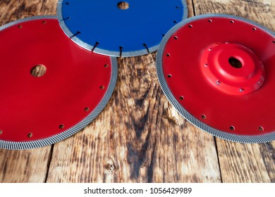 Red diamond wheels for granite and stone, blue for concrete, reinforced concrete, on a wooden old board background