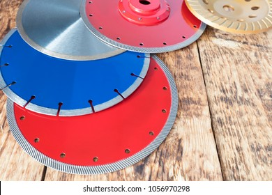 Red diamond wheels for granite and stone, blue for concrete, reinforced concrete, yellow for grinding concrete and stone, silver for cutting ceramic tiles on a wooden old board background