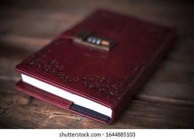 Rotes Tagebuch mit unscharfem Hintergrund auf einem braunen Holztisch.
