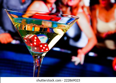 red dice in the cocktail glass in front of gambling table, casino series