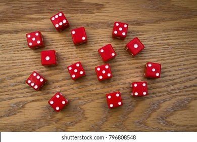 Red DIce Cubes Scattered on an Oak Table