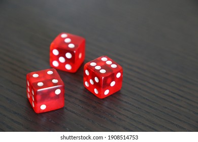 Red dice on dark wooden table. Background for casino games, gambling, luck or randomness