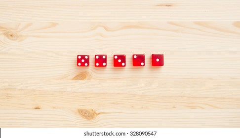 Red dice on wooden background. Concept of gambling, luck and chance.