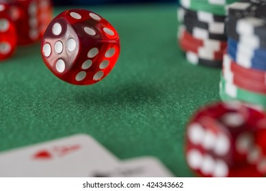 Red dice rotates in the air, casino chips, cards on green felt