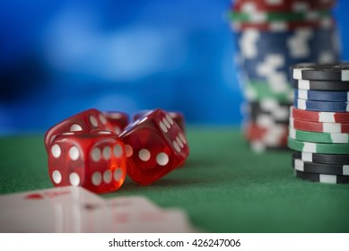 Red dice rotates in the air, casino chips, cards on green felt poker table