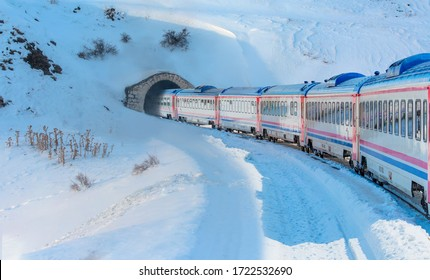 Red diesel train (East express) in motion at the snow covered railway platform - The train connecting Ankara to Kars - Passenger train going through tunnel