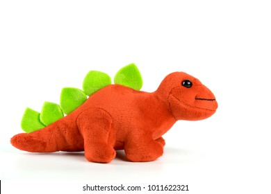Red dinosaur plush toy isolated on white. This dinosaur doll also called stegosaurus