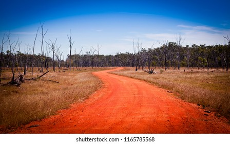 Red dirt road in Australia stretching into the distance. Open road, travel adventure.