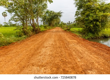 Red Dirt Road Going through Green Field in a Countryside.