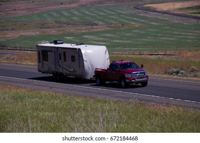 A Red Dodge Pickup-Truck Pulls an RV down a rural US Highway. June 20th, 2017 Oregon, USA