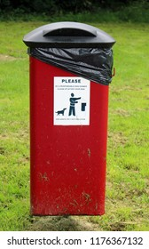 Red dog litter bin on a metal pole seen from the front with advisory sticker and hinged black lid in a park with grass.