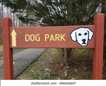 red dog park sign with white dog and asphalt trail